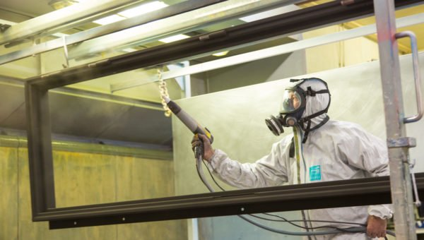 Worker in overalls spraying glass